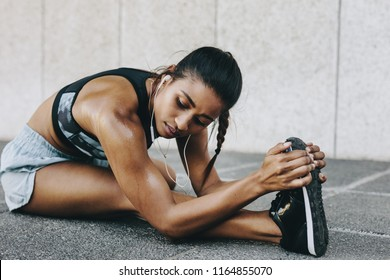 Female athlete doing stretching exercises listening to music sitting outdoors. Fitness woman bending forward stretching her leg sitting on the ground.