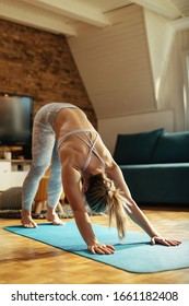 Female athlete in downward facing dog position practicing Yoga at home.