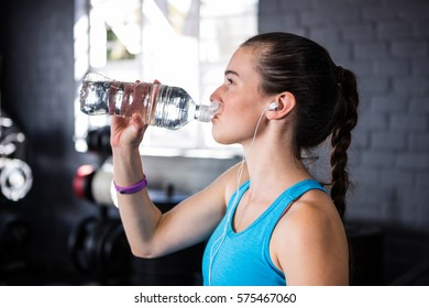Female athlete drinking water while standing in gym