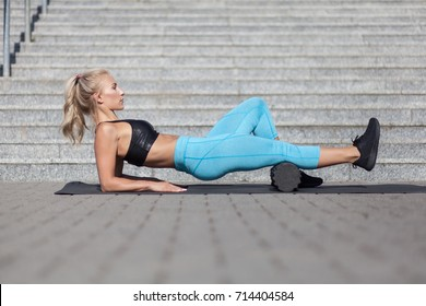 female athlete exercising with fascia roll