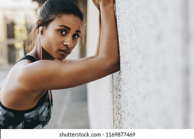 Female athlete exercising outdoors with forearms to a wall. Woman in fitness clothes doing warm up exercises listening to music wearing earphones.