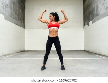 Female athlete flexes arm muscles in outdoor gym area