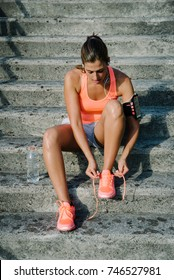 Female athlete getting ready for urban fitness and running training. Sporty woman lacing sport footwear.