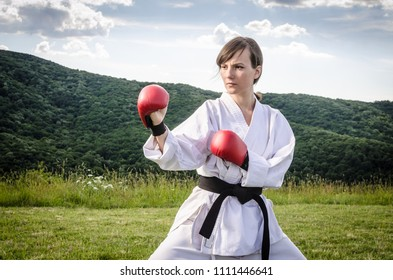 Female athlete with gloves doing karate exercise outdoors. Martial arts.