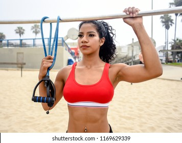 Female athlete holds onto a pull-up bar and resistance bands at an outdoor exercise and fitness area