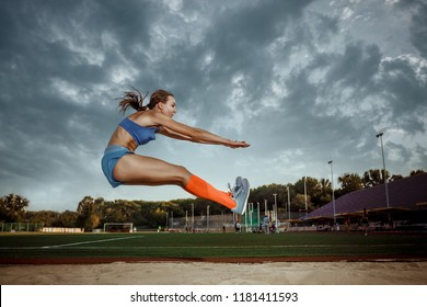 Female athlete jumping during a training at stadium. The jump, athlete, action, motion, sport, success, championship concept