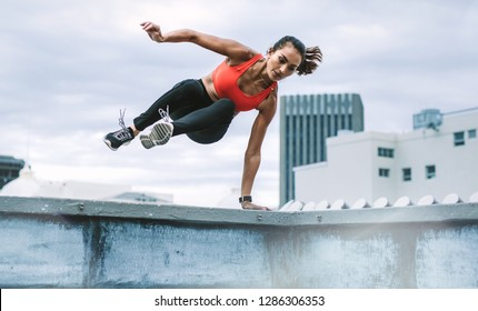 Female athlete jumping on to the rooftop from the roof fence taking support of one hand. Woman in fitness wear jumping from the rooftop fence on to the terrace with both legs in air.