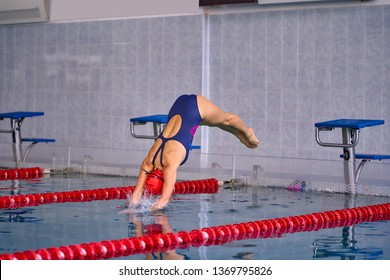 Female athlete jumps to the pool water. Middle-aged woman professionally engaged in swimming.
