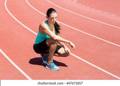 Female athlete kneeling on running track on a sunny day