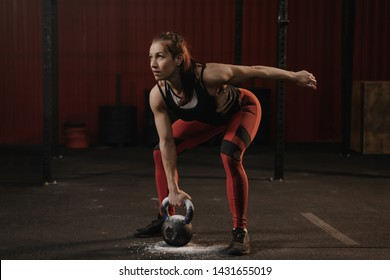 Female athlete lifting heavy weights. Sports woman holding kettlebell while crossfit training. Copy space for text