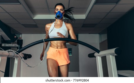 Female athlete with mask running on treadmill to analyze her fitness performance. Runner testing her performance in sports science lab.