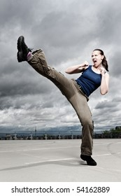 A female athlete performing a turning kick in a dramatic city cloudscape.