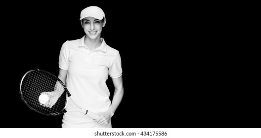 Female athlete playing tennis on black background