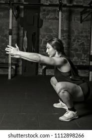 Female athlete practicing air squats