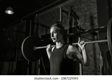 Female athlete practicing back squats