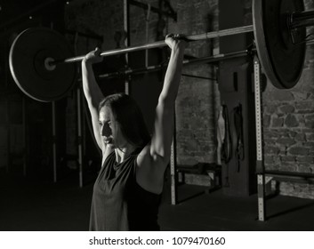 Female athlete practicing clean and jerk movement