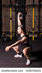 Female athlete practicing kettlebell squats