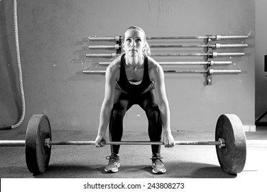 female athlete is preparing to lift deadlift at the gym - focus on the woman