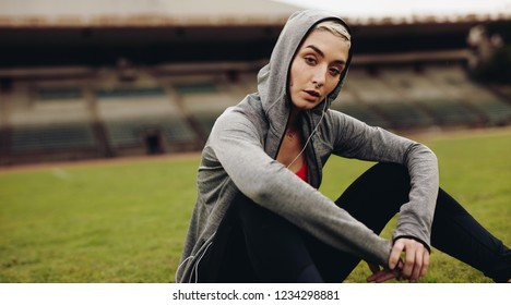 Female athlete relaxing sitting on the ground listening to music. Woman runner in hooded jacket and earphones sitting and relaxing in a track and field stadium.