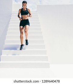 Female athlete running down the stairs of a building. Woman in fitness wear doing workout running downstairs.