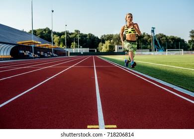 A female athlete runs along the treadmill. Sport background