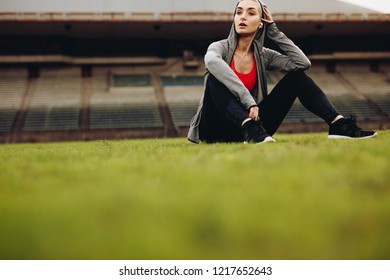 Female athlete sitting on ground and relaxing after workout. Fitness woman taking a break after workout sitting and listening to music.