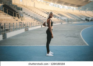 Female athlete standing inside a track and field stadium ready. Female runner getting ready to warm up and workout before running.