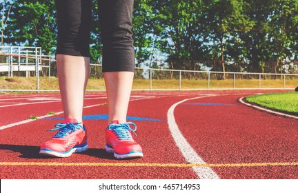 Female athlete standing on a stadium track preparing for a run