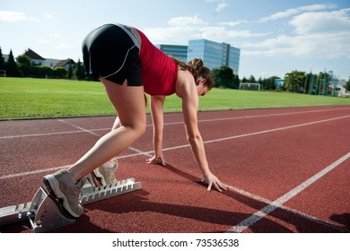 Female athlete in the starting blocks, ready to go