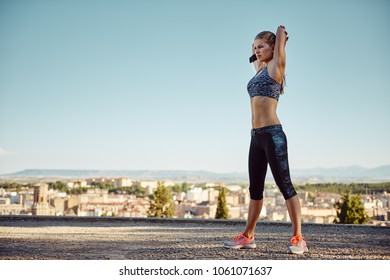 Female athlete stretching arms, exercising outdoor at sunset. Sport, health, lifestyle.