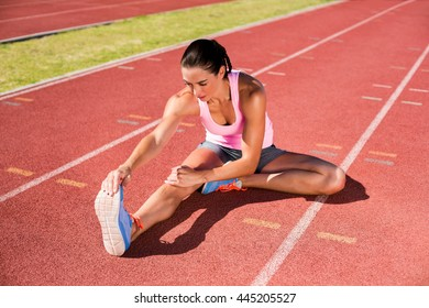 Female athlete stretching her hamstring on running track