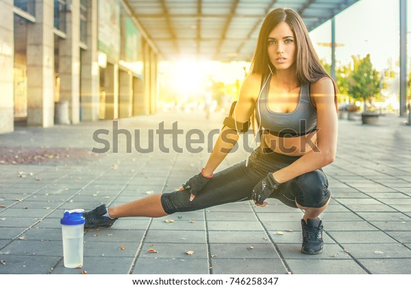 Female athlete stretching her leg before sports training during sunset in urban city area.
