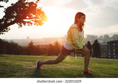 Female athlete stretching legs for warming up before running in city park on sunset or morning. Brunette  sporty woman exercising outdoor.