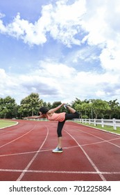 Female athlete stretching legs for warming up before running on stadium track