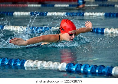 Female athlete swims with a butterfly style. Splashes of water scatter in different directions.
