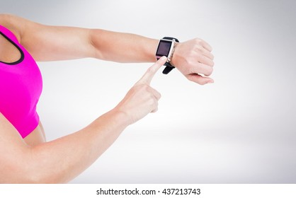 Female athlete using her smart watch against grey background