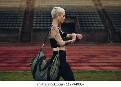 Female athlete walking beside an athletic track looking at her wrist watch. Woman in fitness wear walking in a track and field ground carrying her bag and listening to music.