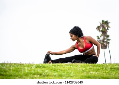 A female athlete wearing red sports bra and black leggings stretches hamstring outdoors