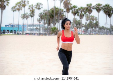 A female athlete wearing red sports bra and black leggings runs on the beach.