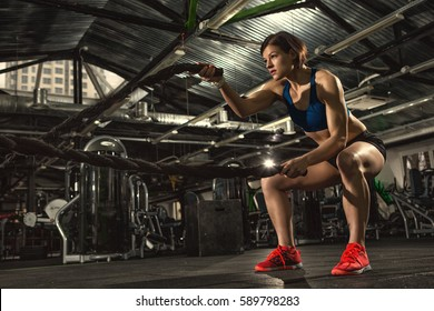 Female athlete working out with heavy ropes at the gym