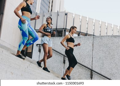 Female athletes jogging down the stairs of a building during the morning run. Group of three fitness women training outdoors climbing down the stairs.