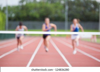 Female athletes running towards finish line on track field