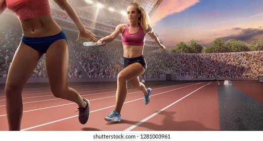 Female athletes sprinting. Runner passes the baton at the running track in professional stadium