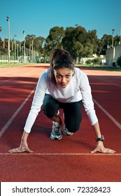 Female athlete/sprinter in 'on your marks, get set, go' starting starting position.