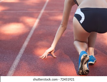 Female athlete/sprinter in 'on your marks, get set, go' starting starting position, shot from behind.