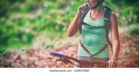 Female athletic drinking water from hydration pack in forest
