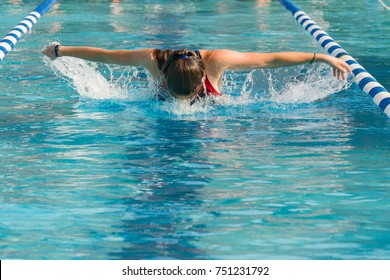 Female athletic swimmer competing in a swim meet in the butterfly stroke