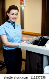 Female attendant posing with cart in hotel corridor