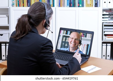 Female attorney-at-law with headset in front of a laptop on her desk giving online advice to an elderly client, legal helpline, copy space