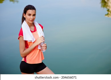 Female attractive runner with the bootle of water in the hands standing on beautiful lake background, jogger resting after run,fitness and healthy lifestyle concept